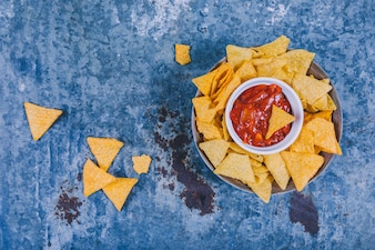 Tasty mexican nachos with salsa sauce on weathered background