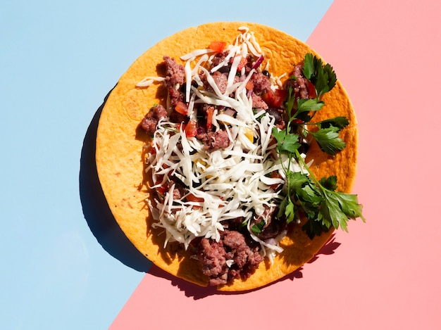 Tasty mexican taco with meat and veggies on contrasted blue and pink background