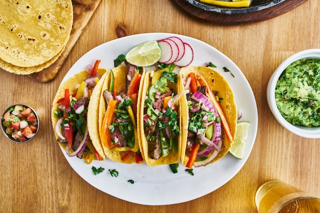 Tasty mexican tacos with beef fajita filling served with salsa and guacamole in flat lay composition