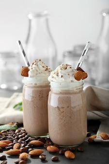 Вкусные коктейли из молочного коктейля с кофейными зернами и миндальными орехами на столе