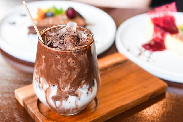 Вкусный молочный коктейль со льдом какао в стекле на деревянном фоне