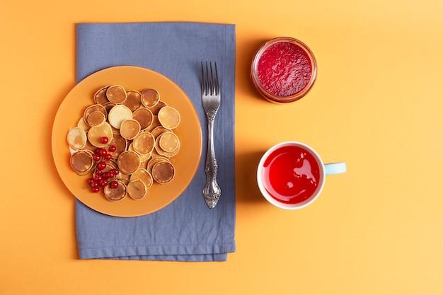 青いナプキンの上にオレンジ色のプレートのおいしいミニパンケーキが立っています