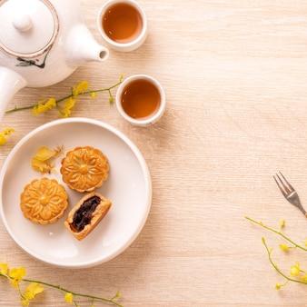 밝은 나무 테이블에 중추절을위한 맛있는 달 케이크, 노란색 꽃으로 장식 된 축제 애프터눈 티의 개념, 평면도, 평면 누워
