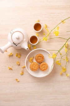 Tasty moon cake for mid-autumn festival on bright wooden table, concept of festive afternoon tea decorated with yellow flowers, top view, flat lay