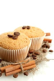 白で分離された黄麻布、スパイス、コーヒーの種のおいしいマフィンケーキ