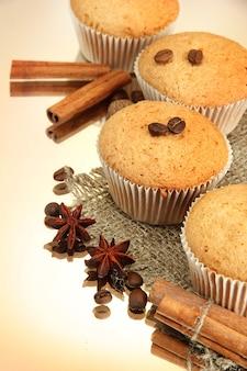 ベージュの背景に、黄麻布、スパイス、コーヒーの種のおいしいマフィンケーキ