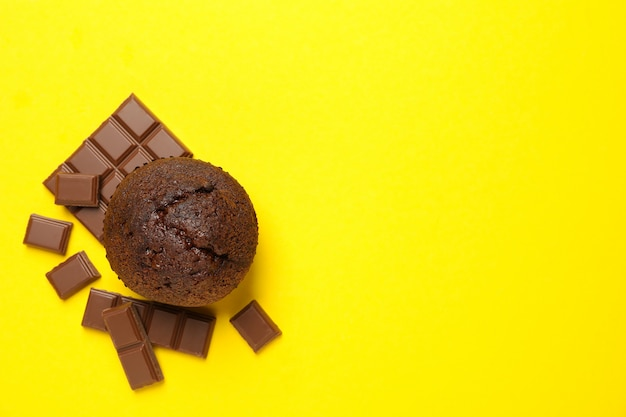 Tasty muffin and chocolate on yellow background, top view