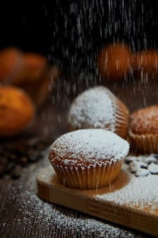 Tasty muffin closeup on a wooden board sprinkled with powdered sugar, selective focus.