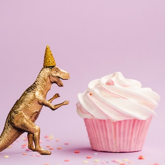 Tasty muffin and dinosaur with birthday hat