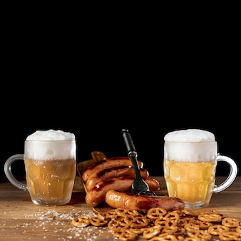 Tasty mugs of beer with sausages on a table