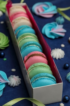 Tasty multi-colored sweet macaroons in a white gift box on a classic blue background, closeup, vertical orientation