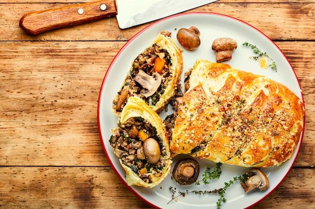 Вкусный грибной пирог или гриб веллингтон на старом деревянном столе. английская еда