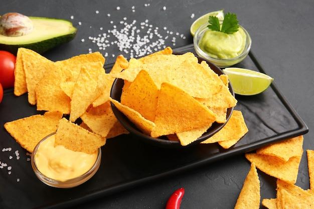 Tasty nachos and sauces on dark table