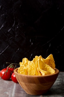 Tasty nachos in wooden bowl and tomatoes