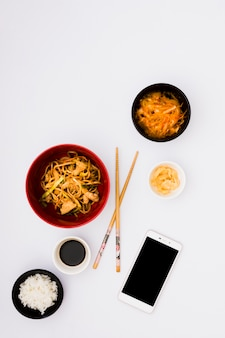 Tasty noodles in bowl near salad; ginger pickle; soya sauce and steamed rice with mobile phone on white background