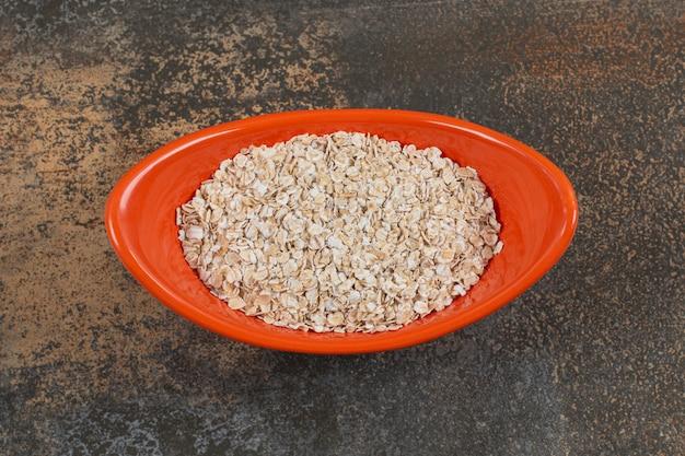 Tasty oat flakes in orange bowl.