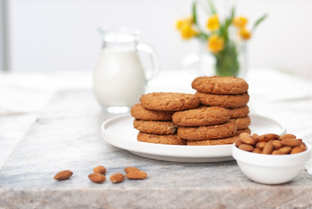Tasty oatmeal and almond cookies with jar of milk on the old marble table