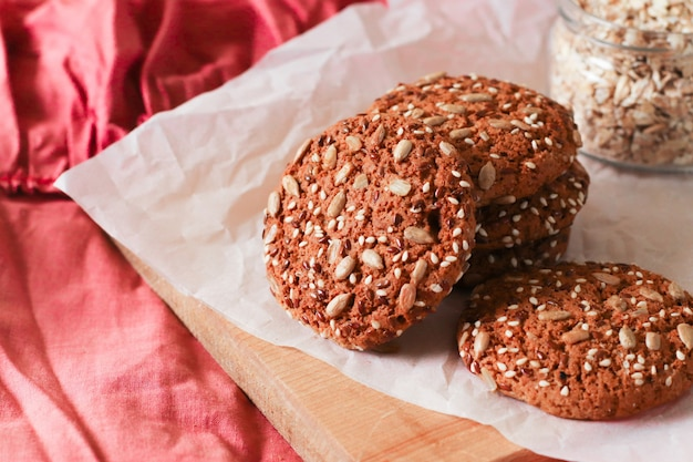 Tasty oatmeal cookies with nuts and seeds on a beige background