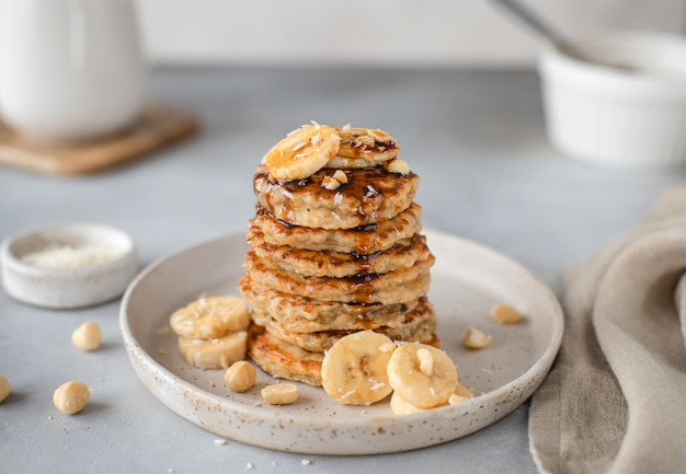 Tasty oatmeal pancake with banana, nuts and date syrup gray surface,