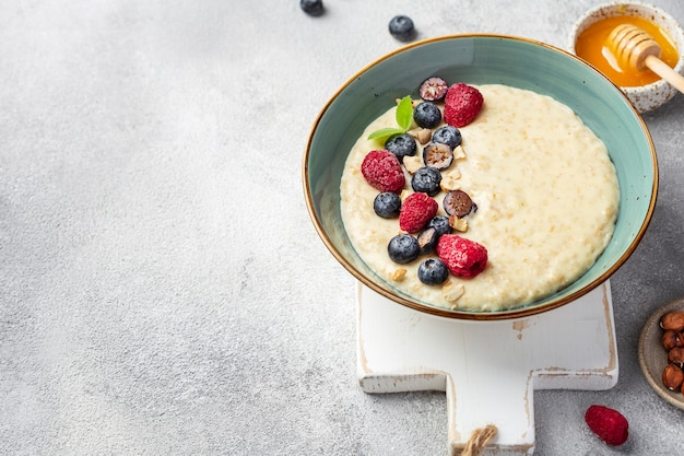 Вкусная овсянка с ягодами в миске на белой поверхности