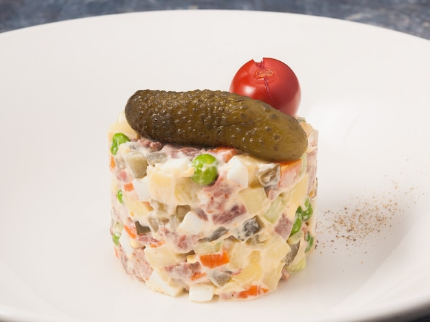 Tasty olivier salad with roast beef on a white plate in a restaurant