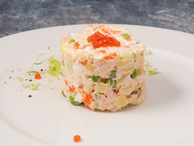Tasty olivier salad with salmon and red caviar on a white plate in a restaurant