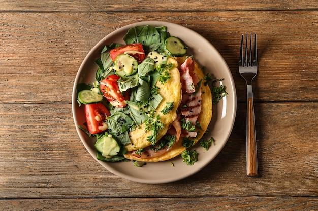 Вкусный омлет с беконом и овощами на тарелке