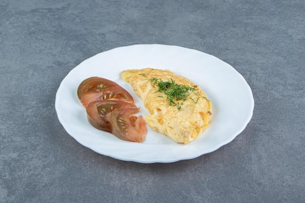 Вкусный омлет и ломтики помидоров на белой тарелке