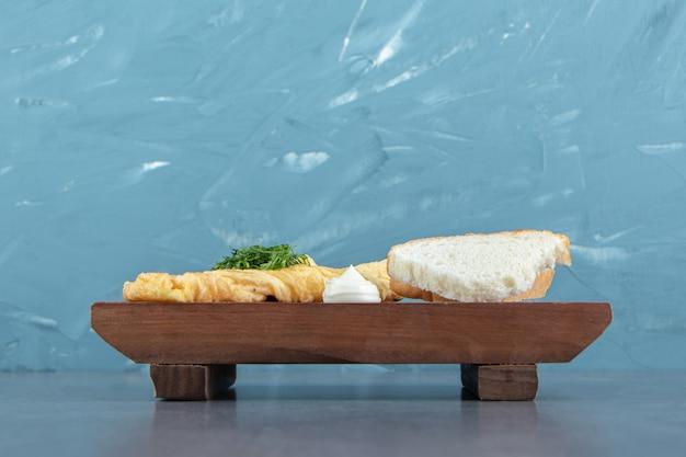 木の板にパンが入った美味しいオムレツ。