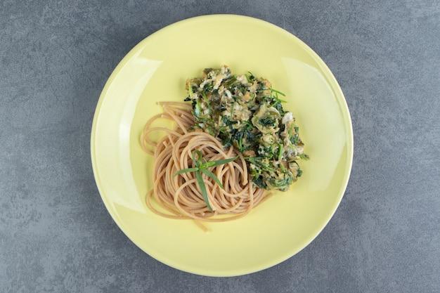 Вкусный омлет с зеленью и спагетти на желтой тарелке.