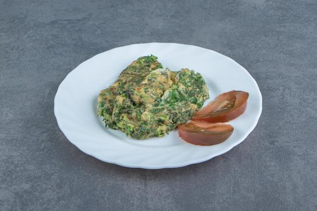Вкусный омлет с зеленью на белой тарелке.