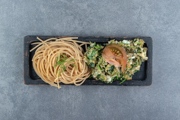 Tasty omelette with greens and spaghetti on black plate.