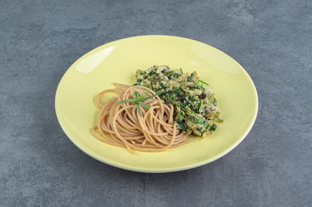Tasty omelette with greens and spaghetti on yellow plate.