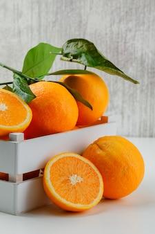 Вкусные апельсины в деревянной коробке с веткой и ломтиками, вид сбоку