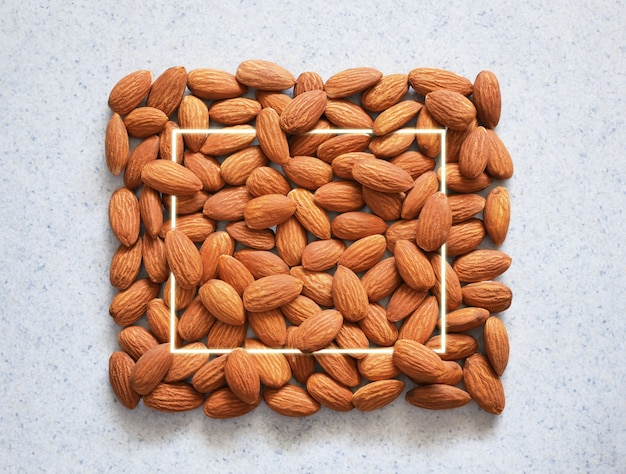Tasty organic almond nuts with square frame. food background.
