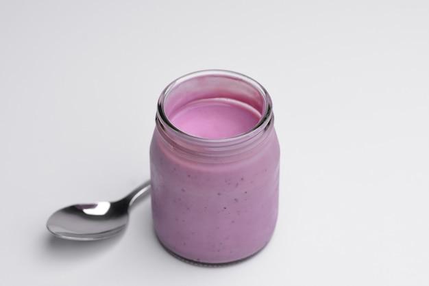 Tasty organic yogurt in glass jar and spoon isolated on white tasty organic yogurt of homemade