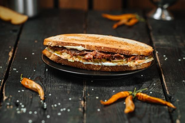 暗い木製のテーブルに美味しいオックステールサンドイッチ