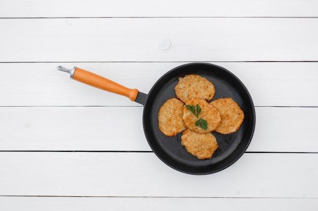 Вкусные блины на сковороде на белом деревянном столе