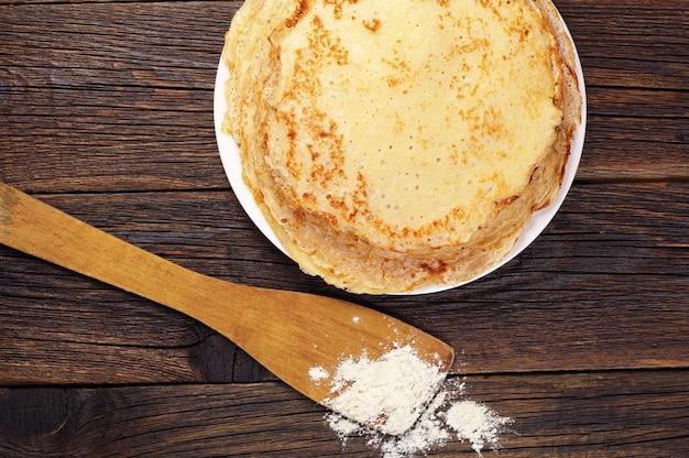 Вкусные блины в тарелке на старинном деревянном столе
