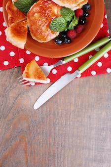 木製の背景に、プレートに新鮮なベリー、蜂蜜、ミントの葉とおいしいパンケーキ