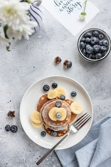 Tasty pancakes with fresh blueberries, banana and powdered sugar on a gray concrete surface. vertical image, top view, flat lay