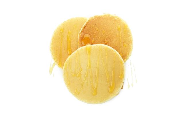 Tasty pancakes with honey isolated on white background