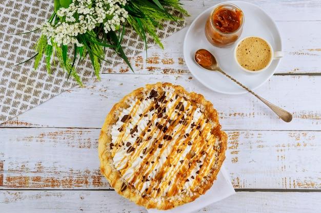 キャラメルソースと白いテーブルでおいしいパーティーケーキ