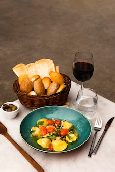 Tasty pasta and basket of bread with wine on table
