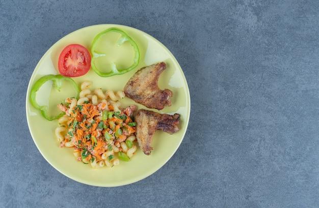 Pasta gustosa e ali di pollo sul piatto giallo.