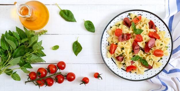 Вкусная паста фарфалле с жареными колбасками, свежими помидорами черри и базиликом на тарелку на белый деревянный стол. вид сверху, плоская планировка. баннер