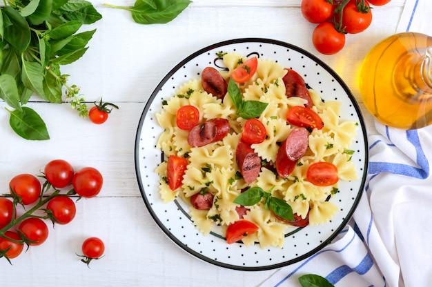 Вкусная паста фарфалле с жареными колбасками, свежими помидорами черри и базиликом на тарелку на белый деревянный стол. вид сверху, плоская планировка.