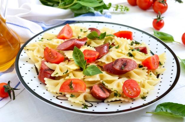 Вкусная паста фарфалле с жареными колбасками, свежими помидорами черри и базиликом на тарелку на белый деревянный стол.