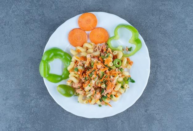 白い皿に刻んだ野菜のおいしいパスタ。