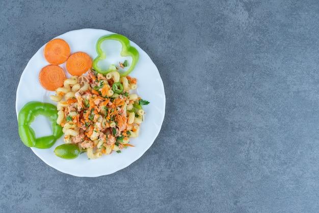 하얀 접시에 다진 야채와 함께 맛 있는 파스타.